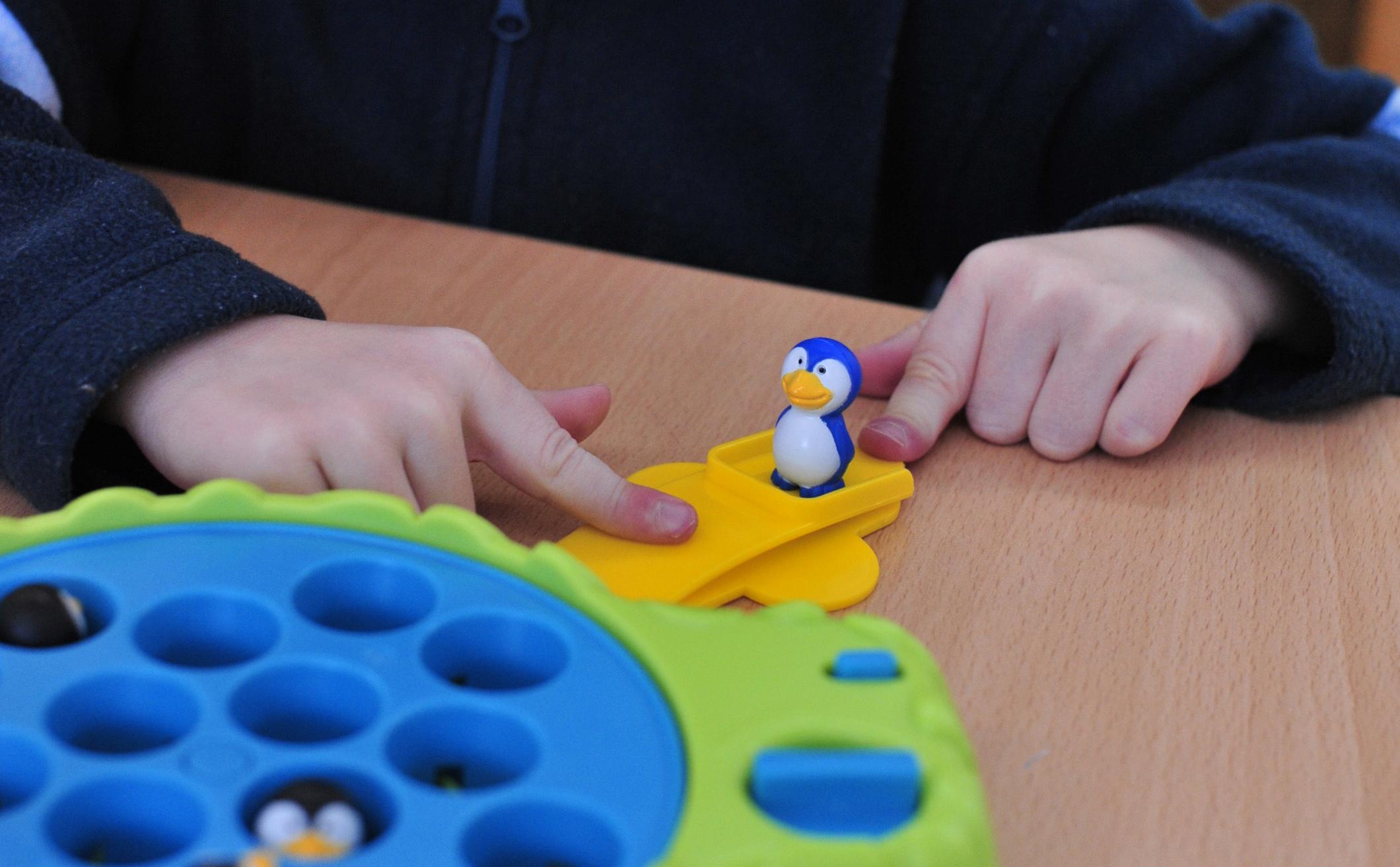 Kinderhände spielen mit einem blauen Pinguin auf einer gelben Plattform
