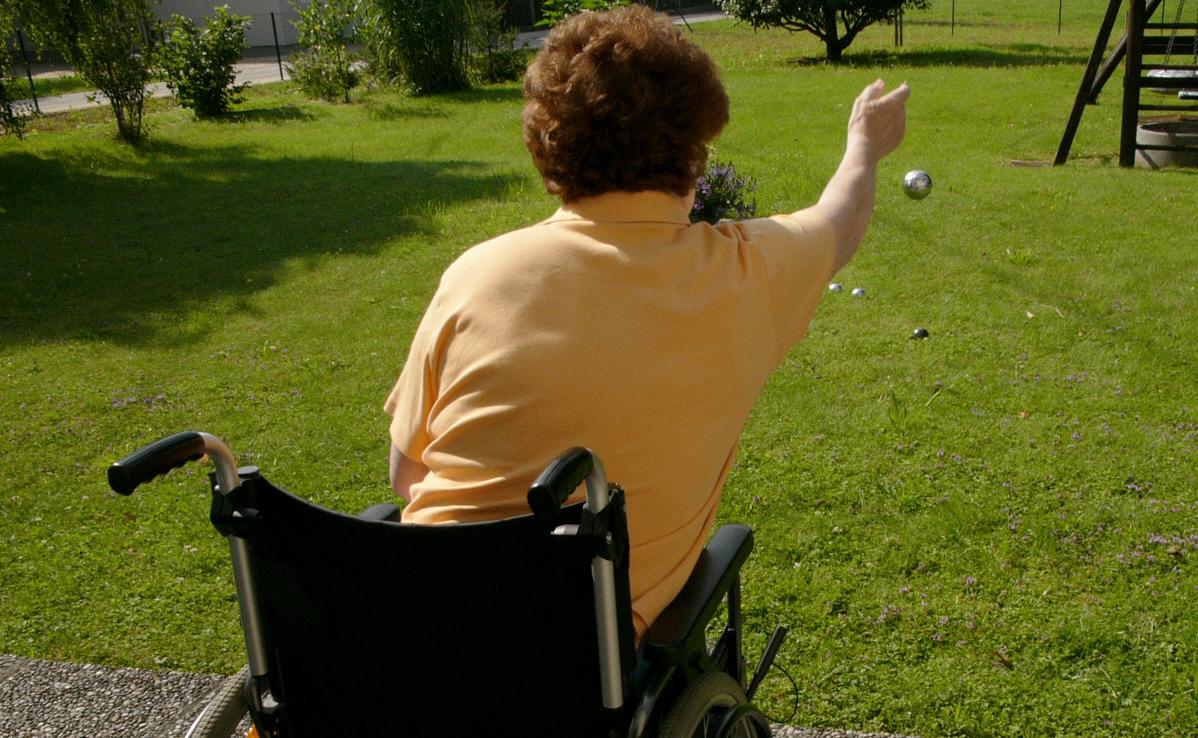 Eine Frau spielt vom Rollstuhl aus Boccia
