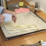 Abbildung zweier Hände beim Bestreuen von geschnittenem Blätterteig mit Salz