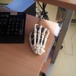 Plastikskeletthand auf einer Computermaus